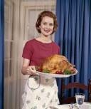 1960s Woman Serving Thanksgiving Turkey Dinner